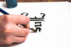 Process of calligraphy lettering. Background. Unrecognizable artist`s hand drawn word inspire with ink on white paper. Drawing lessons, art school, creativity Royalty Free Stock Photos