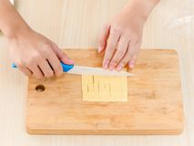 The process of chef cooking - cutting cheese pieces. On cutting board Stock Image