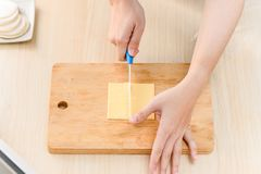 The process of chef cooking - cutting cheese pieces. On cutting boardn Royalty Free Stock Images