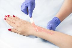 The process of classical wax depilation of female limbs. In the beauty salon royalty free stock photography
