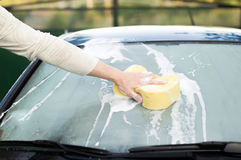 The process of cleaning the windows of the car using shampoo and Royalty Free Stock Photography