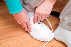 Process of clothing of white sports sneakers Stock Photo