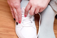 Process of clothing of white sports sneakers Stock Photos