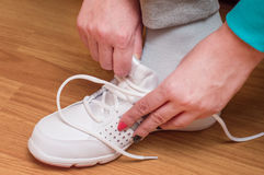 Process of clothing of white sports sneakers Stock Image