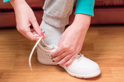 Process of clothing of white sports sneakers Royalty Free Stock Image