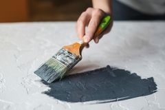 Process of coloring in dark grey color textured concrete surface for desk. Stock Photography