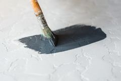 Process of coloring in dark grey color textured concrete surface for desk. Royalty Free Stock Photos