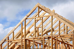 The process of construction of a frame private house. The process of construction of a frame private house with a pitched roof. Wooden frame on the blue sky Stock Photos