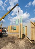Construction of new and modern modular house. Process of construction new and modern modular house from composite sip panels. Vertical photo of crane with wall stock photos