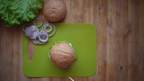 The process of cooking a burger directly above the wooden table . stock video footage