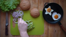 The process of cooking a burger directly above a wooden table. stock video footage