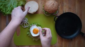 The process of cooking a burger directly above a wooden table. stock footage