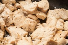 The process of cooking chicken breast diet for an athlete in a frying pan in sunflower oil. Meat for muscle recovery after stock photography