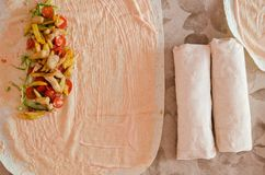 Cooking chicken wrap. The process of cooking chicken wrap on kitchen table at home concept. Homemade kebab close up. Fresh thin lavash or pita bread roll of royalty free stock image