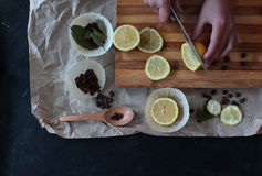 Process of cooking in the kitchen, boy holding half a lemon in h. Is hands, on the table next to slices of lemon and coffee beans and green spices royalty free stock photos