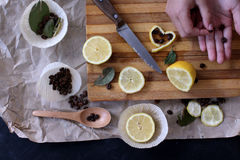 Process of cooking in the kitchen, boy holding half a lemon in h. Is hands, on the table next to slices of lemon and coffee beans and green spices stock photo