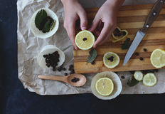 Process of cooking in the kitchen, boy holding half a lemon in h. Is hands, on the table next to slices of lemon and coffee beans and green spices stock photography