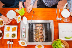 Process of cooking Korean barbecue raw pork on the tabletop grill in restaurant. Selective focus. close up. Stock Images
