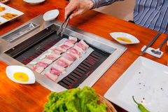 Process of cooking Korean barbecue raw pork on the tabletop grill in restaurant. Selective focus. close up. Stock Photos