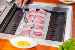 Process of cooking Korean barbecue raw pork on the tabletop grill in restaurant. Selective focus. close up. Stock Image