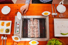 Process of cooking Korean barbecue raw pork on the tabletop grill in restaurant. Selective focus. close up. Stock Photography