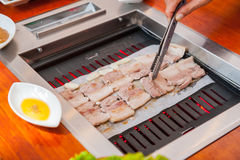 Process of cooking Korean barbecue raw pork on the tabletop grill in restaurant. Selective focus. close up. Royalty Free Stock Image