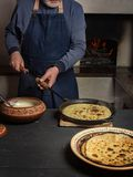 Process of cooking pancakes in a wood stove. royalty free stock images