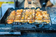 The process of cooking shish kebab on a metal grill in the open. Air.Grilling shashlik on barbecue grill. Marinated meat Stock Images