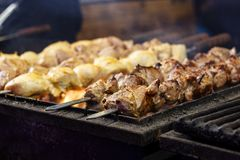 The process of cooking shish kebab on a metal grill in the open. Air.Grilling shashlik on barbecue grill. Marinated meat Royalty Free Stock Image