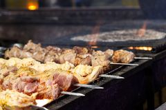 The process of cooking shish kebab on a metal grill in the open. Air.Grilling shashlik on barbecue grill. Marinated meat Stock Image