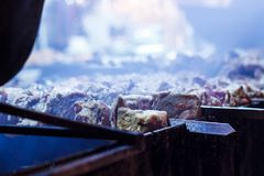 The process of cooking shish kebab on a metal grill in the open. Air.Grilling shashlik on barbecue grill. Marinated meat Stock Photos