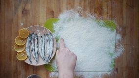 The process of cooking a small fish, preparing for frying in oil in a frying pan. Top view of a man with a finger writing the word fish in flour on a green stock footage