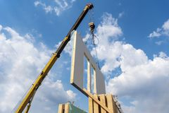 Construction of new and modern modular house. Process of crane construction of new and modern modular house from composite sip panels against background with stock photo
