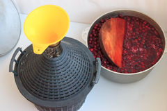 The process of creating cherry wine. Transfusion of fermented cherries in the bottle for wine Royalty Free Stock Photo