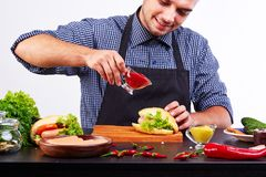 A young guy in an apron makes a fresh hot dog. royalty free stock photos
