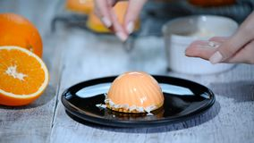 Process of creating delicious dessert. Unrecognizable confectioner hands decorate orange glazed cakes. Process of creating delicious dessert. Unrecognizable stock footage