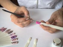The process of creating a drawing on tips. Nail art design. royalty free stock photos