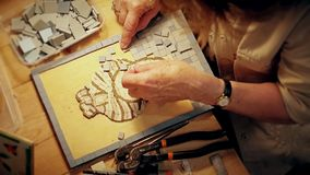 Process creating modern antique portrait by tiled mosaic in creative workshop