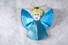 The process of creating your own Christmas angel from a disposable cardboard plate, a plastic spoon and paper. Christmas decor. Handmade, hobby, DIY stock images