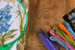 The process of cross-stitch. Canvas on hoops, needles, embroidery floss and pattern. Copy paste Stock Photos