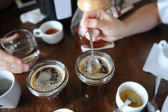 The process of cupping. Tasting freshly brewed coffee with spoons. Coffee accessories on the table Stock Photos