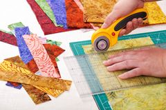 Process cutting fabric pieces by rotary cutter on mat using ruler Stock Image