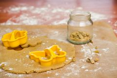 Process of cutting gingerbread in the form of butterflies and flowers and a can of cardamom seeds stock photography