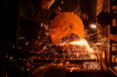 Process of cutting metal tubes on the machine. Sparks are flying in different directions in the dark stock image