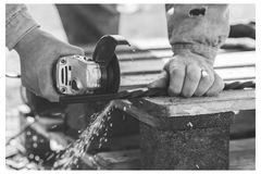 The process of cutting metal using the angle grinder. Grayscale effect and frame. The process of cutting metal using the angle grinder. Ukraine Stock Image