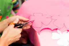 Womans hands cutting out cloth flower Royalty Free Stock Images