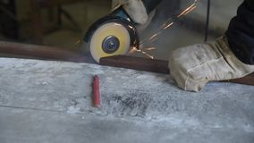 Process of cutting rectangular metal profile using the electric angle grinder, sparks fly around, specialist skill. S. Work process closeup. Preparation of parts stock footage