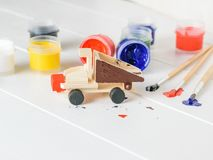 The process of decorating a wooden truck toy on a white table. stock images