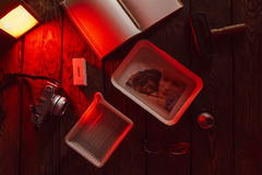 Process of developing film photography. The process of developing film photography in the light of the red lamp on the wooden table. workplace of photographer Stock Photo