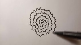 The process of drawing a spiral flower black liner.